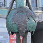 Figur einer Frau mit aufgebrochenem Globus als Rock.