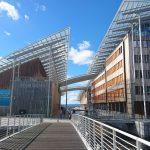 Steg vor modernem Gebäude mit Glasdach und Holzfassade