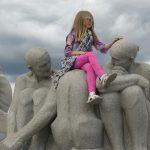 Kinder sitzen auf großen Steinfiguren